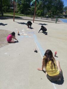 Four individuals making hearts using sidewalk chalk