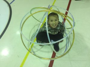 child sitting in the middle of a ball of hoola hoops