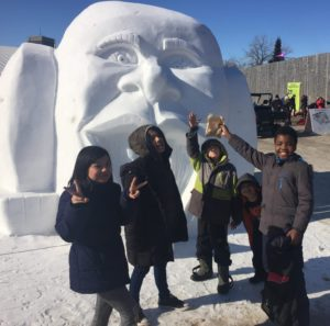 Group of 5 children standing in front of a snow sculpture
