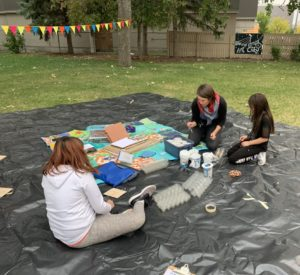 One adult and two children sitting on a large tarp making crafts