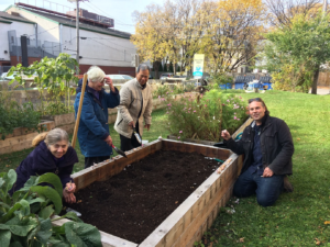 four adults stand by a raised garden bed