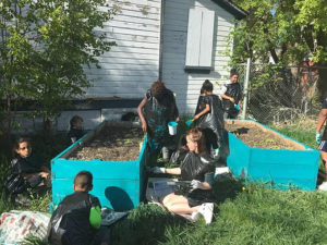 a group of people, mostly kids, outside painting garden boxes