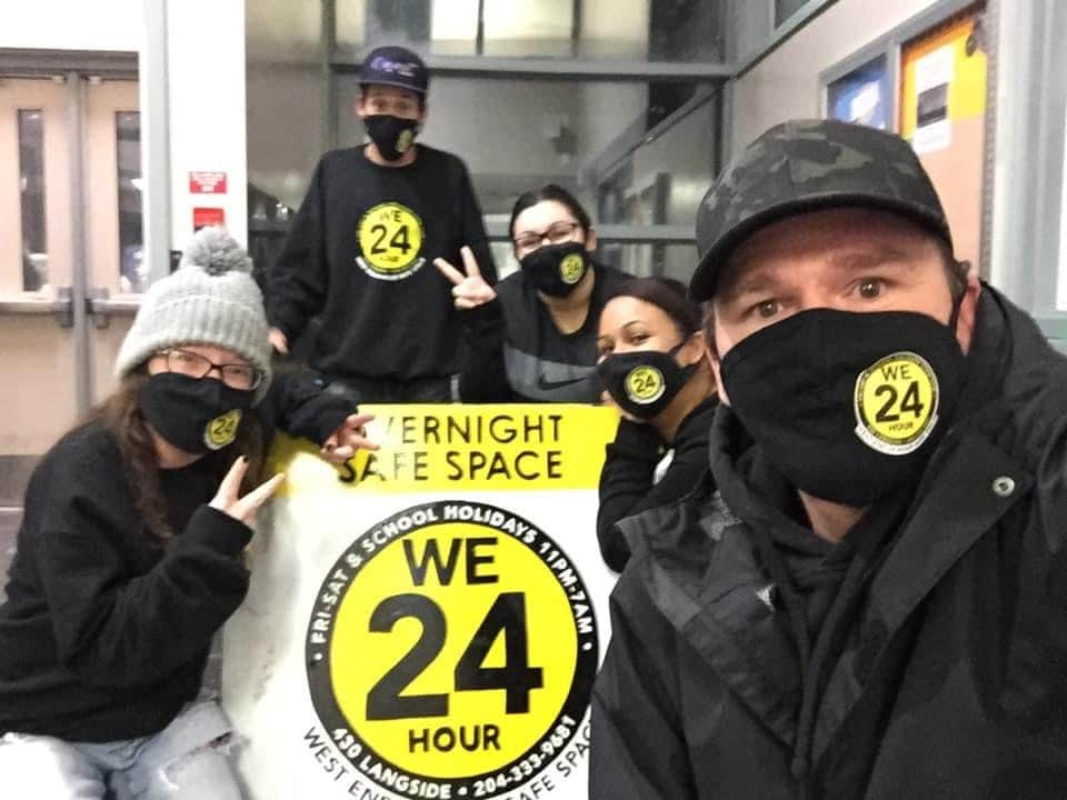 group of people with masks on standing around a sign that says WE24
