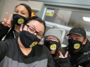 four individuals wearing masks one making peace sign