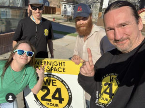 group of four individuals standing around a sign that says WE24
