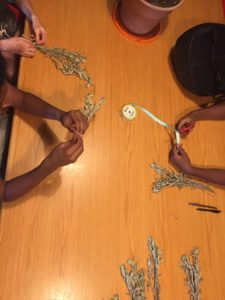three young people sitting at a table tying sage into bundles