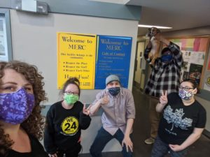 past & present WE24 staff wearing masks standing in the lobby at MERC