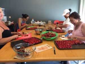 group of volunteers sitting around a table with a lot of strawberries in containers