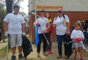 group of people with garbage bags and garbage pick up tools