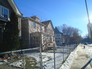 street view of houses with wire fencing in front during winter