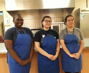 three woman stand wearing aprons