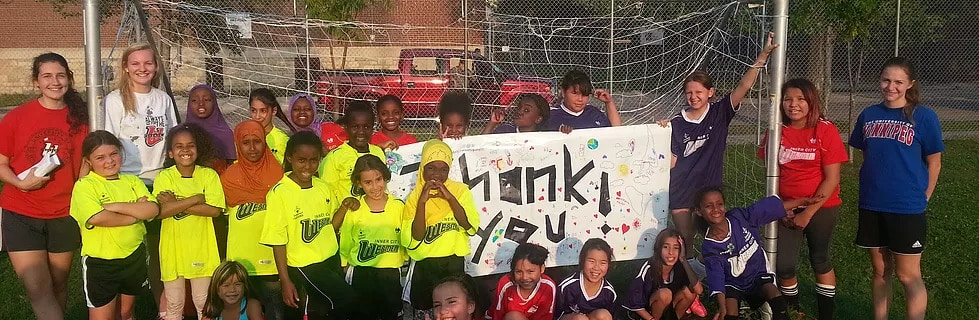 a youth sports team grouped together, smiling
