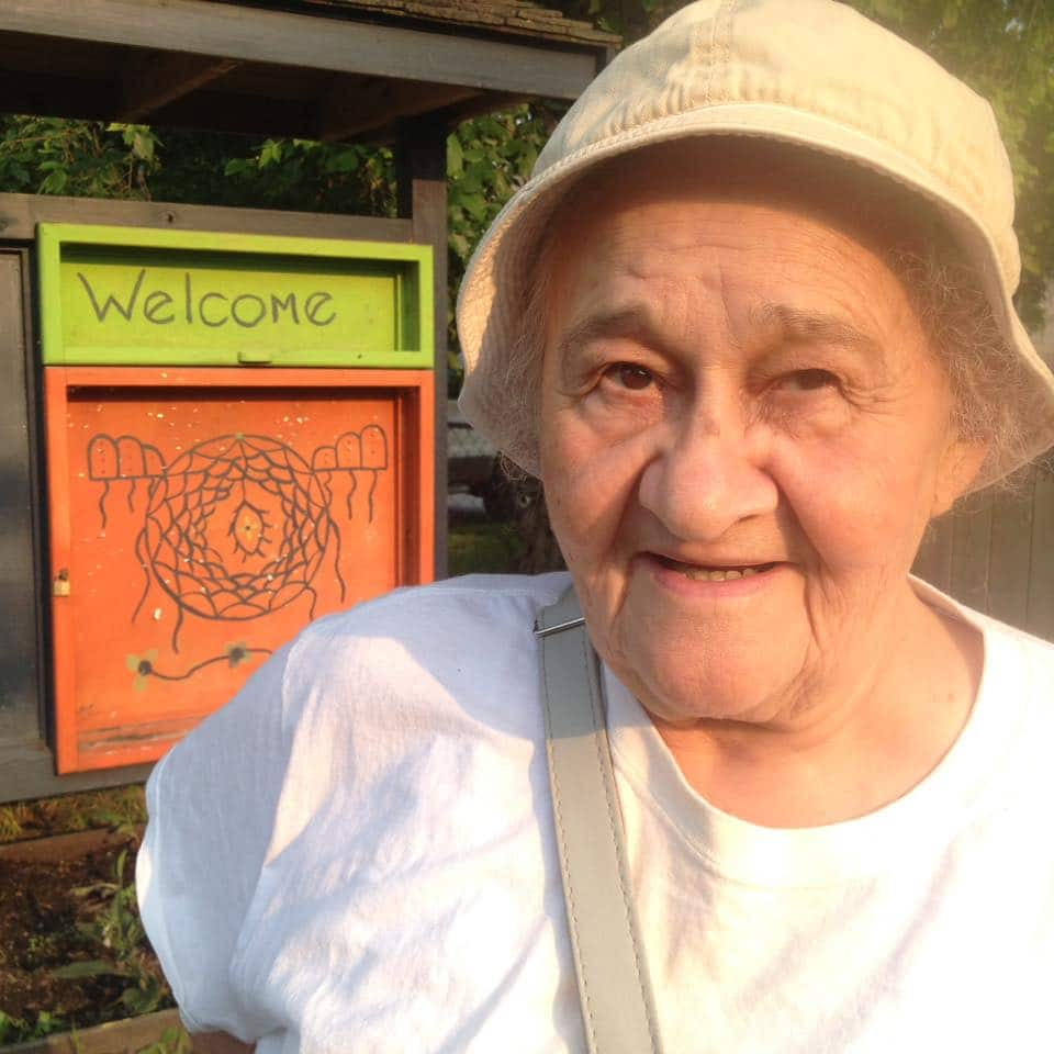 An older woman, Geraldine, stands next to a small indigenous art piece. It says welcome.