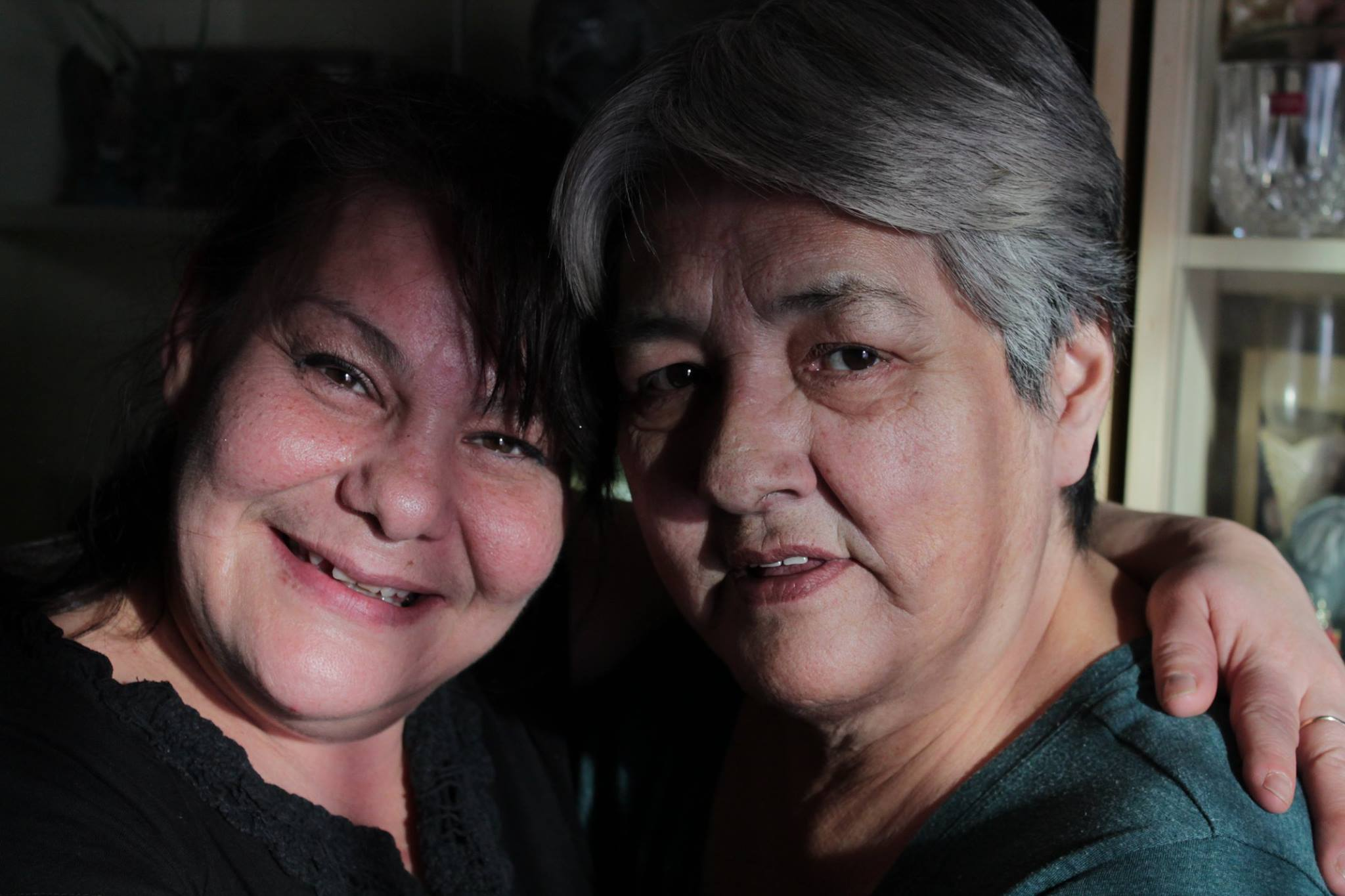 Two women, Kim and Thelma, stand close together arm in arm