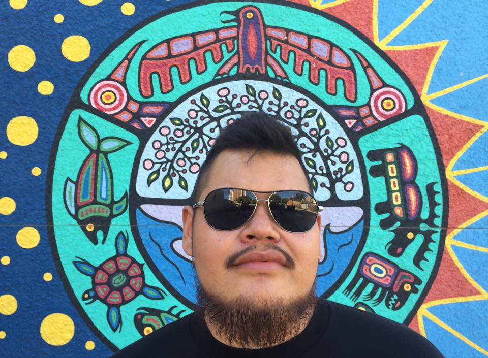 Leonard stands in front of a beautiful indigenous art piece