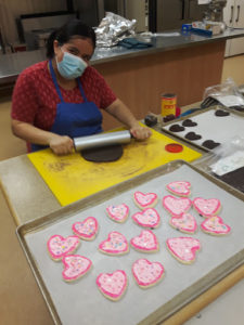 young woman rolling out dough with finished cookies on a platter in from of her